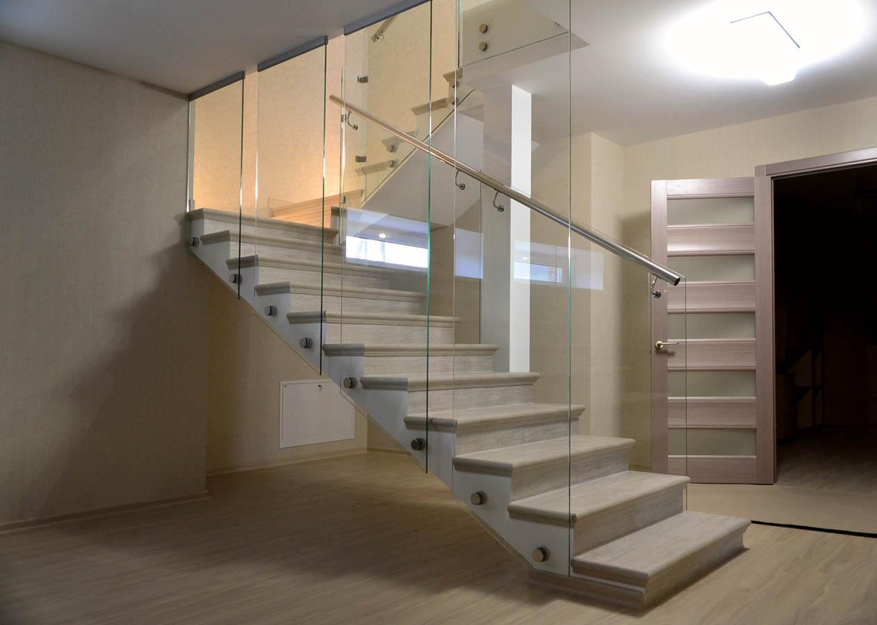 Маршевая лестница с уникальными стеклянными ограждениями и нержавеющим поручнем в загородном доме