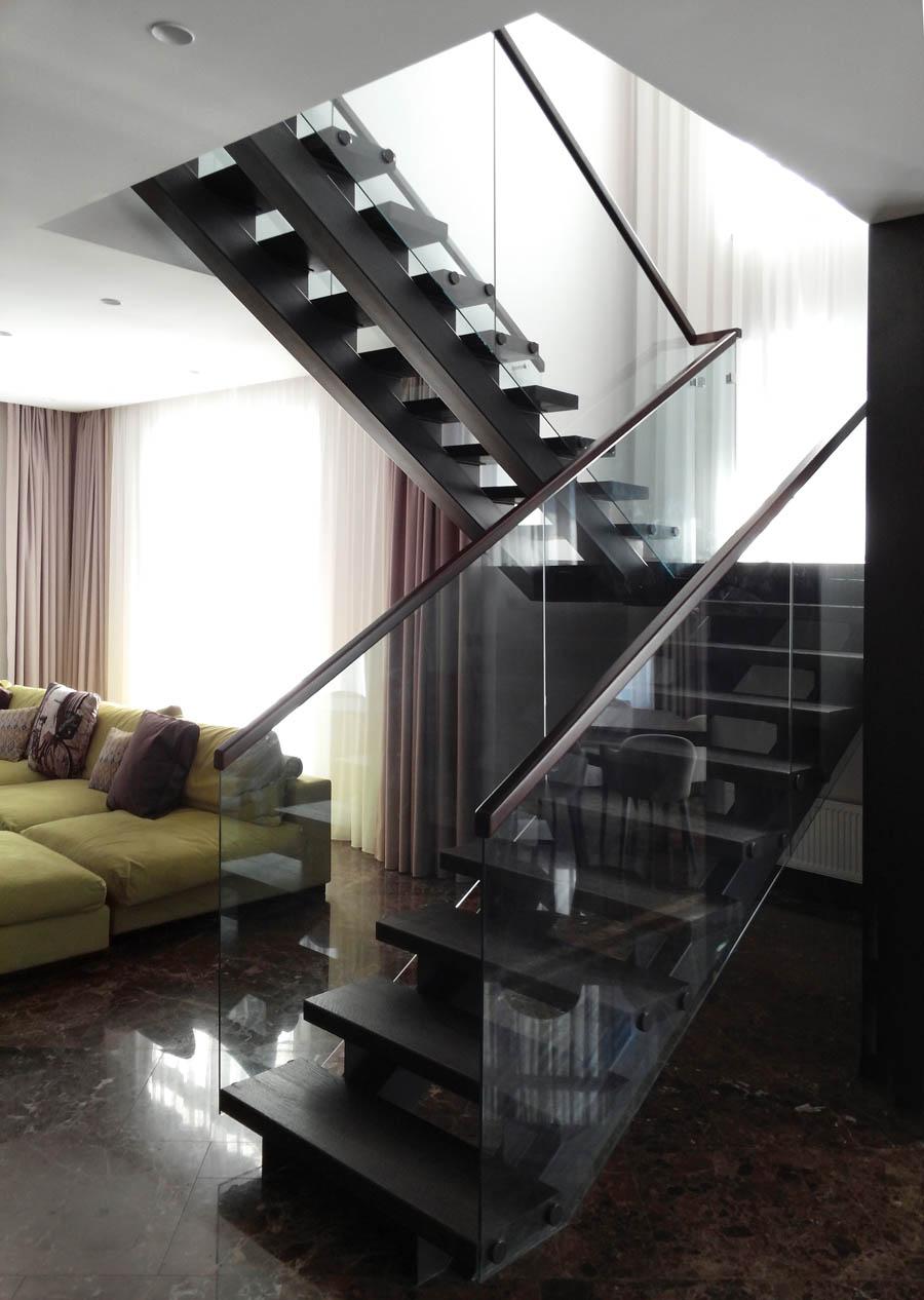 Компактная лестница с темными деревянными ступенями, цельностеклянными ограждениями и тонкими деревянными поручнями