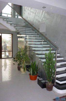 Угловая лестница с темными ступенями, прозрачными ограждениями и перилами из нержавеющей стали