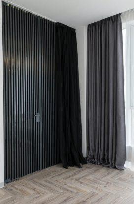 Стеклянная дверь в темном алюминиевом обвязе с вертикальными полосами в квартире