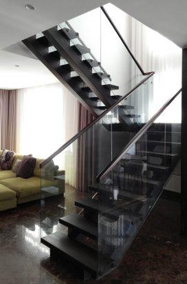 Стеклянное ограждение лестницы с деревянным поручнем в квартире
